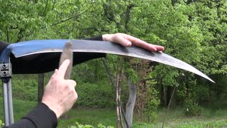 scythe sickle -with-stone-in-spring-farm-